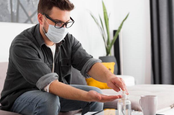 Man in woning met handgel en masker